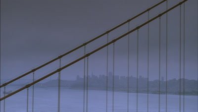 Medium wide angle view through cables of Golden Gate Bridge to Downtown skyline and San Francisco Bay beyond