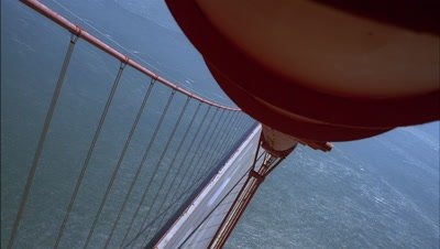 Wide angle very high top shot looking down cable onto road deck and streaming traffic from North tower