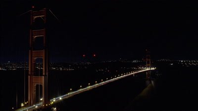 Wide angle floodlit Golden Gate bridge oblique thru frame with constant stream of car headlights crossing