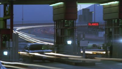 Mid shot two lanes at road level of toll booths with constant stream of traffic and headlights