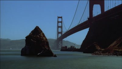 Low wide angle Golden Gate Bridge from shore looking up with blue sky and classic view of bridge