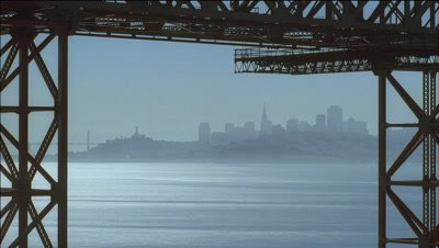 Wide angle view through pilings of Golden Gate Bridge across San Francisco Bay with boats passing through to Downtown skyline beyond
