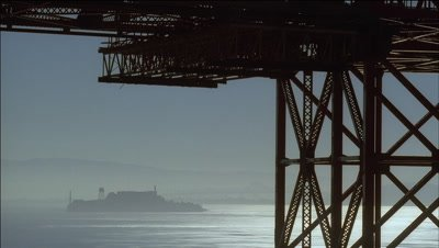 Medium wide angle view through pilings of Golden Gate Bridge across San Francisco Bay featuring Alcatraz