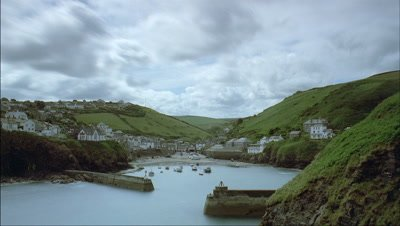 Wide angle clouds race back over land behind traditional coastal fishing port as tide goes out - matches RK10089
