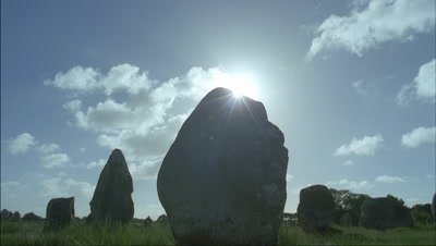 Medium wide angle large standing stone with sun glimpsing around with more stones behind and blue sky with fluffy white clouds racing over
