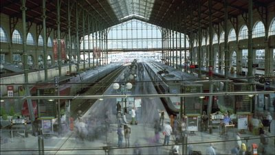 Wide angle view down and over platforms in glass roofed station Gard du Nord with trains and passengers coming and going