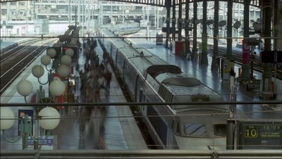 Mid shot view down and over platform in glass roofed station Gard du Nord with train and passengers arriving - matches RK 10103