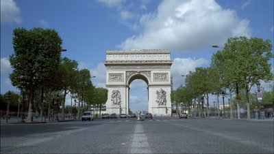 Medium wide angle view to Arc de Triomphe from centre of road with traffic passing either side of camera, blue sky and clouds racing over monument