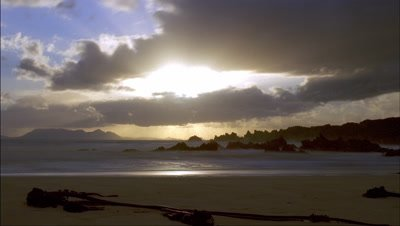 Medium wide angle sandy beach with distant silhouette of Table Mountain as sun sets through dramatic clouds and god rays