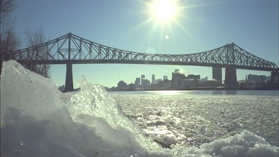 Medium wide angle Montreal city skyline and low tracking sun viewed across an icy St Lawrence River and under bridge span