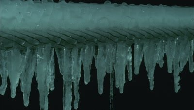 Close up ice forms icicles all along length of taut cable - more extreme