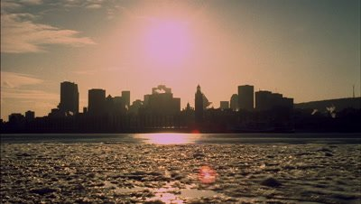 Medium wide angle late afternoon sun sets over Montreal city skyline viewed across a mainly thawed St Lawrence River