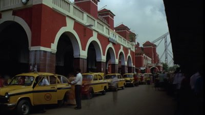 Medium wide angle busy taxi rank outside Howrah Railway Station -Kolkata- with yellow taxis and pedestrians constantly departing and moving along