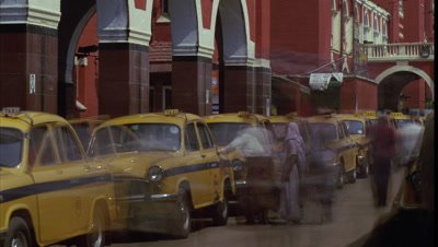 Mid shot busy taxi rank outside Howrah Railway Station -Kolkata- with yellow taxis and pedestrians departing -matches RK 10237