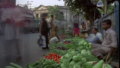 Low wide angle roadside vegetable sellers with pedestrians streaming passed and stopping to buy with mainly foot traffic and tuk-tuks behind