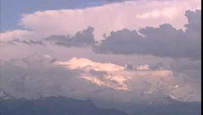 Big wide angle snowy Himalayan mountain scape with rolling and gathering clouds hitting summits
