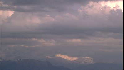 Big wide angle snowy Himalayan mountain scape with rolling and gathering clouds moving over peaks