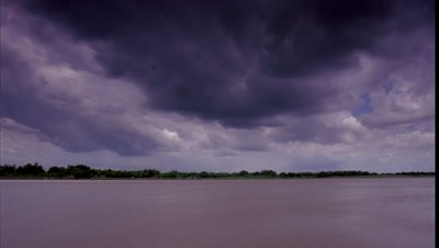 Low wide angle River Ganges filling one third frame in foreground with two thirds blue sky and gathering rain clouds racing overhead towards camera
