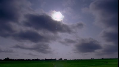 Wide angle big blue sky with low scudding transparent rain cloud with sun rising and flaring overhead with strip of green paddy fields