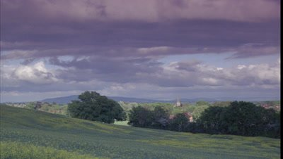 Medium wide angle looking across flowering yellow rapeseed field to English woodland, distant hills and church spire with building clouds overhead