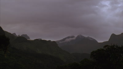 Medium wide angle dark silhouetted peaks of Mt Stanley with glacier atop and dark grey early evening cloud swirling overhead