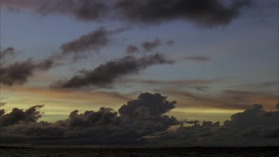 Medium wide angle fluffy dark grey cloud on a backdrop of early morning blue, orange and yellow sky over water as light lifts and sky brightens to blue