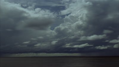 Medium wide angle multiple layers of boiling rain clouds scudding low over dark water which turn to heavy rain showers then darkness