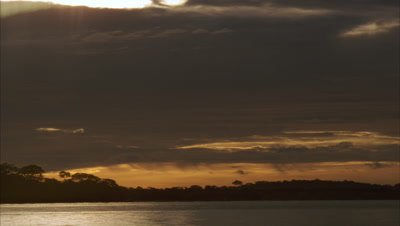 Medium wide angle stormy golden sunset sky with black silhouetted land and water, boatman travels in and out of shot