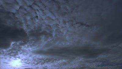 Medium wide angle mackerel sky cloud moves slowly overhead towards camera as sun glimpses through