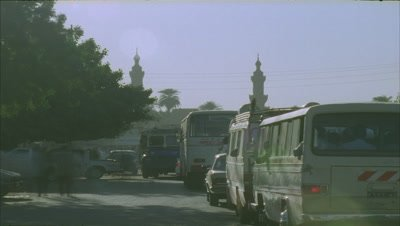 Mid shot busy dusty road with traffic flowing both sides of camera and mosque on skyline