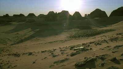 Medium wide angle shadows lengthen and sun sets behind group of pyramids surrounded by sandy dunes