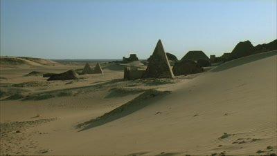 Medium wide angle pyramids in full sun with visitors coming and going then quietens as sun lowers and buildings are enveloped in dark shadow