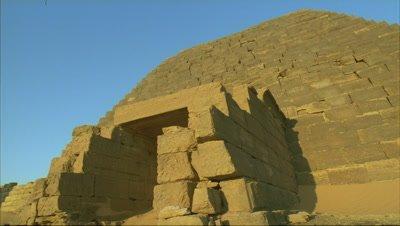 Mid shot low angle of doorway entrance to pyramid emerges from darkness as sun gradually illuminates pyramid