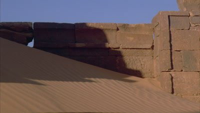 Mid shot ancient pyramid stone blocks in sand as shadow creeps across frame and plunges pyramid into darkness