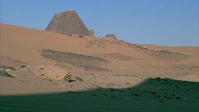 Medium wide angle pyramid on ridge of sand dune with blue sky behind, shadow moves across and engulfs scene in darkness