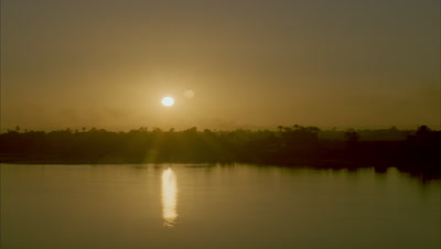 Wide angle soft golden sun sets over River Nile sinking into tree-silhouetted horizon as sky darkens