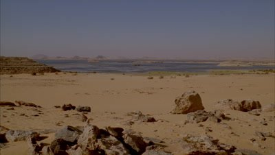 Wide angle over dry sandy desert scape as day breaks with soft multi-coloured sky featuring River Nile in behind