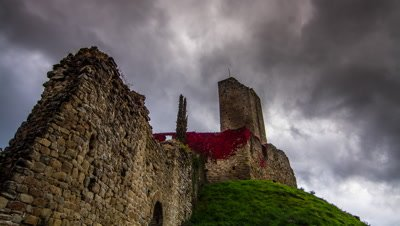 Storm clouds pass over a wide angle shot of a ruined castle