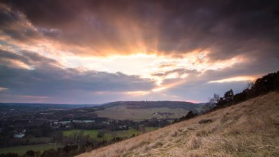 Dramatic sunset from hill top view point in Surrey, UK. A town can be seen in the valley below and good crepuscular rays appear as clouds move through frame.