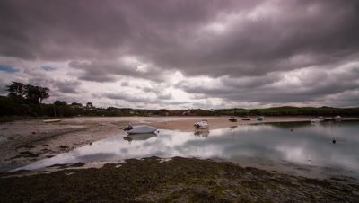 Pan across Cornish estuary as the tide recedes. Good billowing clouds heading towards the camera. Various boats revealed in estuary as the camera pans across and tide visibly drains.