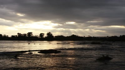 Wide angle Zambezi River above Falls looking across water to silhouetted tree lined river bank with god rays through stormy evening clouds