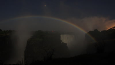 Medium wide angle looking from bridge to motion blurred Falls at night and spectacular lunar rainbow rises over falls with stars
