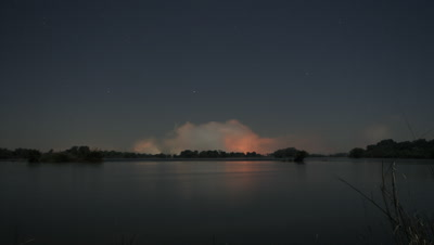 Wide angle Zambezi River across still water to dramatic orange spray rising at top of falls and stars rising above