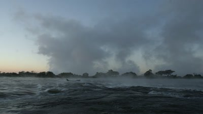 Medium wide angle Zambezi River above Falls looking across turbulent water to great plumes of rising spray at Falls