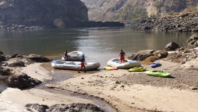 Medium wide angle river beach with three rafts and rafters preparing to go then putting in at Rapid no 11 on the Zambezi