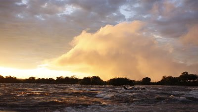 Mid shot looking across rough water above Falls in firey evening light with spray cloud rising from Falls behind then sun and light goes dark