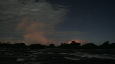 Medium wide angle dark Zambezi River looking across motion blur water to dramatic orange spray rising at top of falls and stars rising above