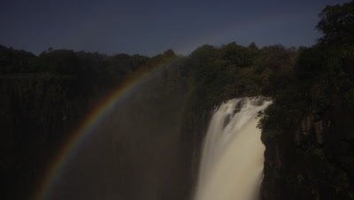 Mid shot looking across single fall of motion blur water - Devil's Cataract - to woodland beyond at night with lunar rainbow