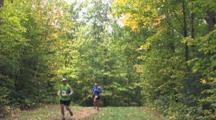 Foot Race Through Autumn Woods, Duo Of Runners Passes