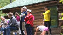 Spectators, Runners Warming Up, Standing Near Warming House On Race Trail